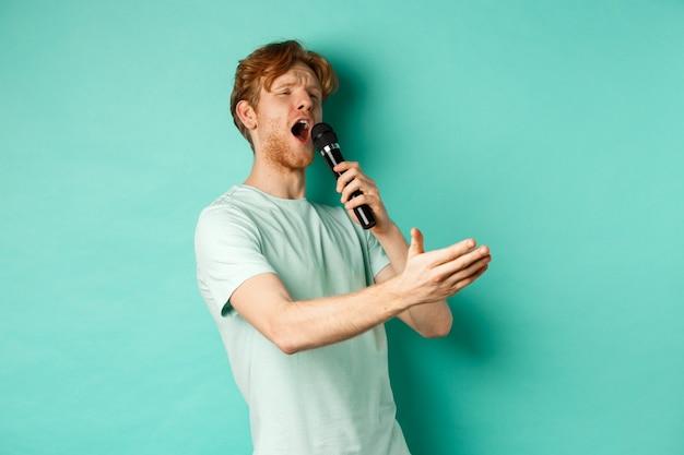 Homem ruivo apaixonado em uma camiseta cantando serenata com microfone, olhando de lado para o karaokê e gesticulando, em pé sobre o fundo de hortelã.