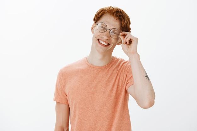 Homem ruivo atraente alegre sorrindo e parecendo despreocupado, usando óculos