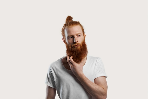 Homem ruivo atraente tenta se lembrar de uma nova ideia, coça a barba ruiva e desvia o olhar com expressão cética