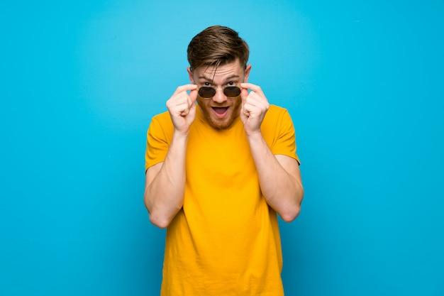 Homem ruivo azul muro com óculos e surpreso
