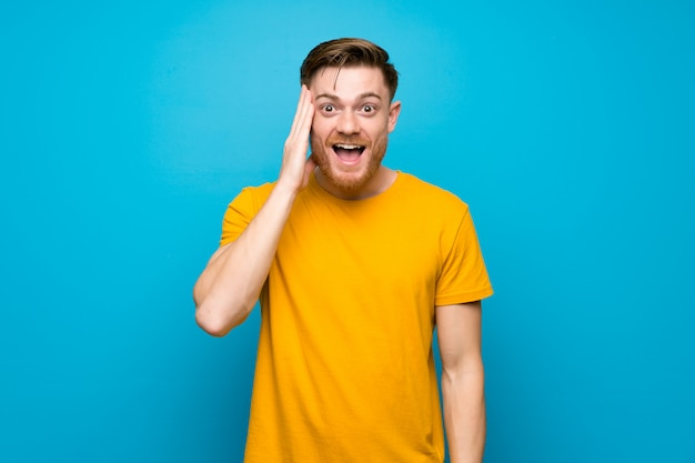 Homem ruivo azul muro com surpresa e chocada expressão facial