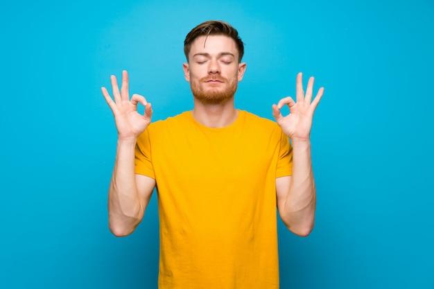 Homem ruivo azul muro em pose de zen