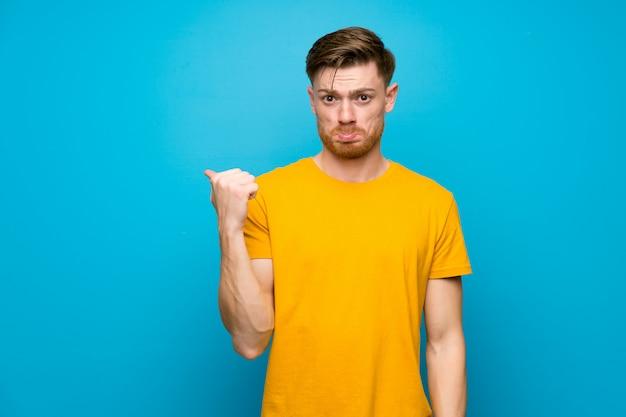 Homem ruivo azul muro infeliz e apontando para o lado