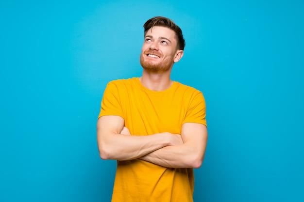 Homem ruivo azul muro olhando para cima enquanto sorrindo