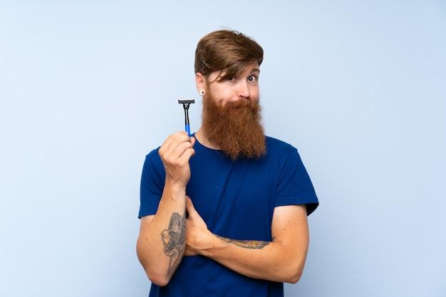 Homem ruivo barbear a barba sobre parede azul isolada, fazendo dúvidas gesto enquanto levanta os ombros