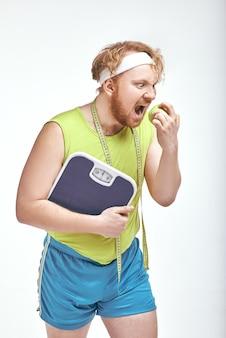 Homem ruivo barbudo e gordo segurando uma maçã e escamas