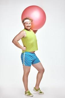 Homem ruivo barbudo gordo segurando uma bola de fitness