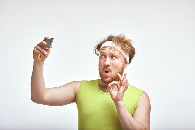 Homem ruivo barbudo gordo sorrindo e tirando uma selfie