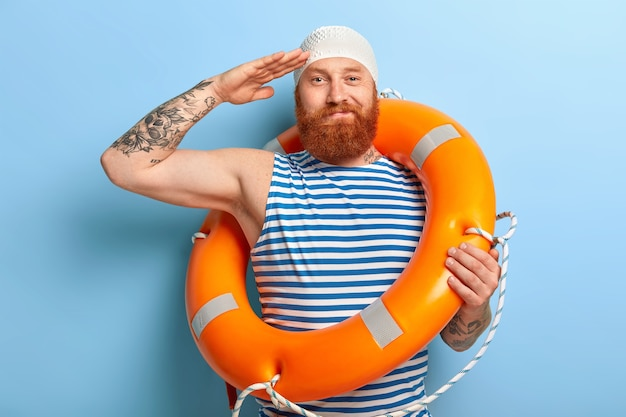 Homem ruivo barbudo satisfeito posando com itens de praia