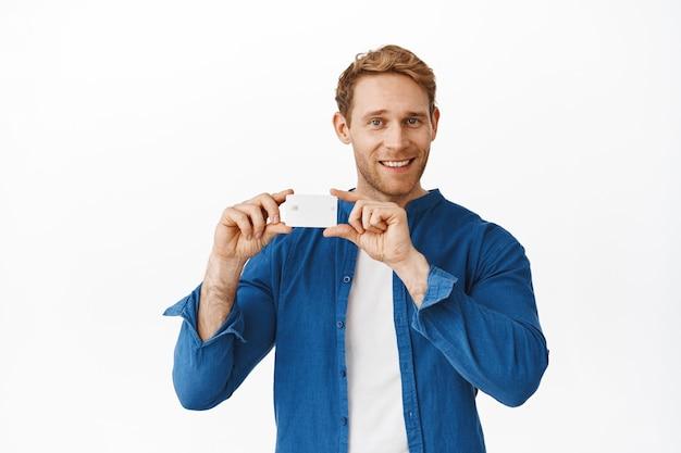 Homem ruivo bonito mostrando seu cartão de crédito e sorrindo satisfeito, anúncio de banco, compras ou promoção de descontos especiais, em pé sobre uma parede branca
