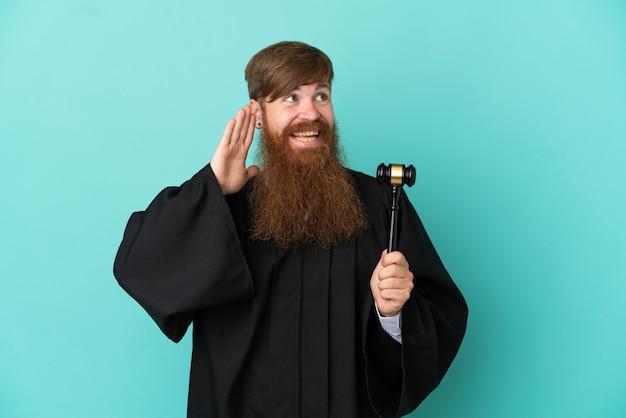 Homem ruivo, branco, juiz, isolado em um fundo azul, ouvindo algo colocando a mão na orelha