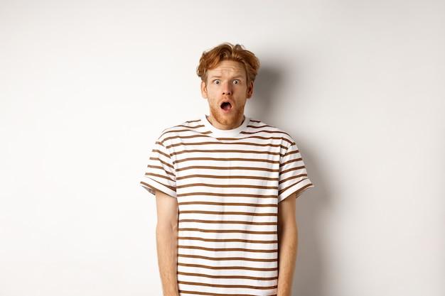 Homem ruivo chocado e assustado gritando, boca aberta e olhando aterrorizado para a câmera, em pé sobre um fundo branco.