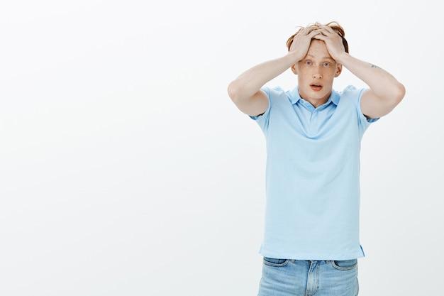 Homem ruivo chocado e confuso agarra a cabeça e parece preocupado, tem um grande problema