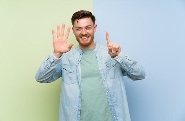 Homem ruivo colorido parede contando seis com os dedos