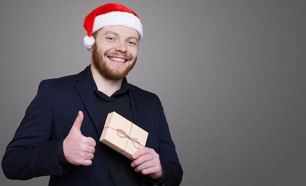 Homem ruivo com barba e chapéu de papai noel gesticulando parecido na parede cinza segurando um presente e sorrindo