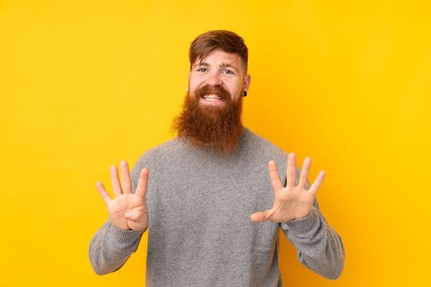 Homem ruivo com barba longa ao longo da parede amarela isolada, contando nove com os dedos