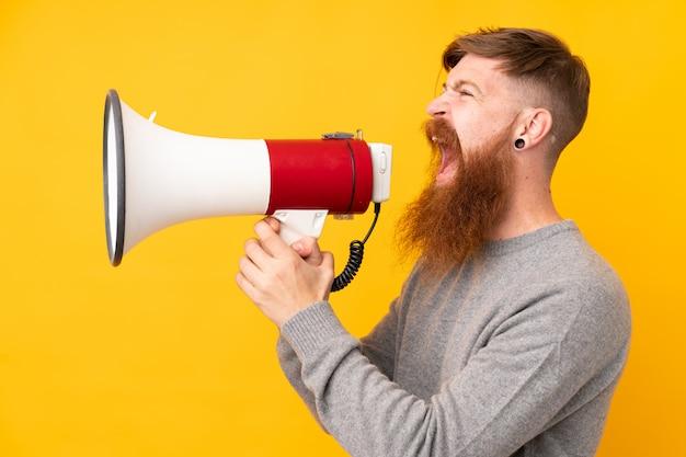 Homem ruivo com barba longa ao longo da parede amarela isolada, gritando através de um megafone