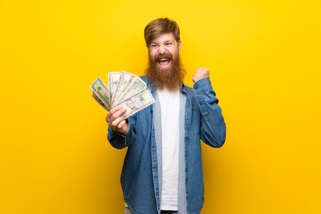 Homem ruivo com barba longa ao longo da parede amarela isolada, levando muito dinheiro