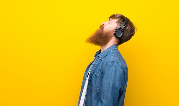 Homem ruivo com barba longa ao longo da parede amarela isolada, ouvindo música com fones de ouvido