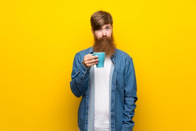 Homem ruivo com barba longa ao longo da parede amarela isolada, segurando a xícara de café quente