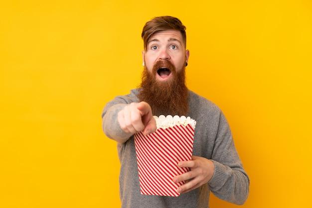 Homem ruivo com barba longa ao longo da parede amarela isolada, segurando um grande balde de pipocas enquanto aponta a frente