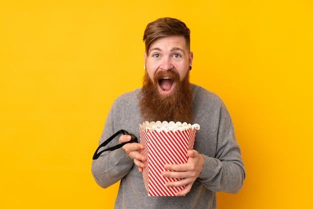 Homem ruivo com barba longa ao longo da parede amarela isolada, segurando um grande balde de pipocas