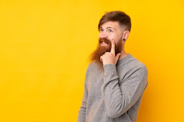 Homem ruivo com barba longa ao longo da parede amarela, pensando uma idéia enquanto olha para cima