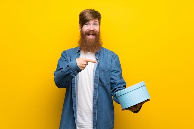 Homem ruivo com barba longa ao longo da parede amarela, segurando a caixa de presente