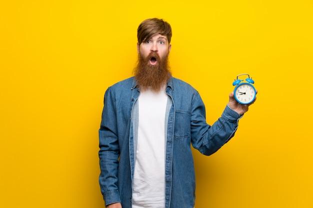Homem ruivo com barba longa ao longo da parede amarela, segurando o despertador vintage