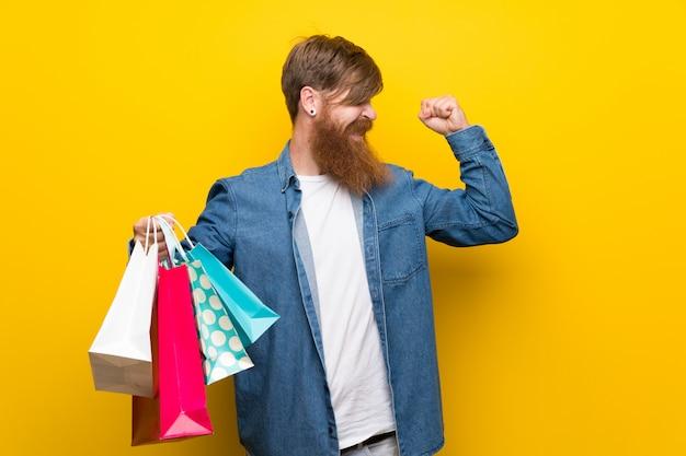 Homem ruivo com barba longa ao longo da parede amarela segurando um monte de sacolas de compras