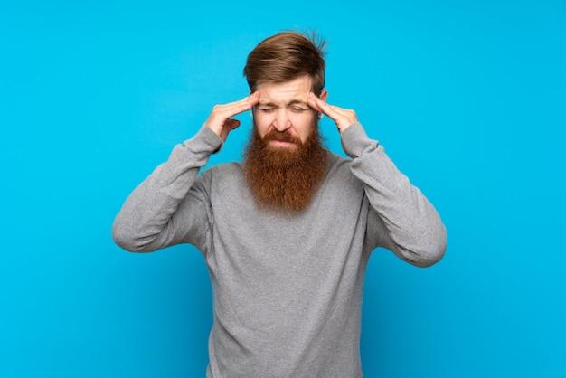 Homem ruivo com barba longa ao longo da parede azul com dor de cabeça