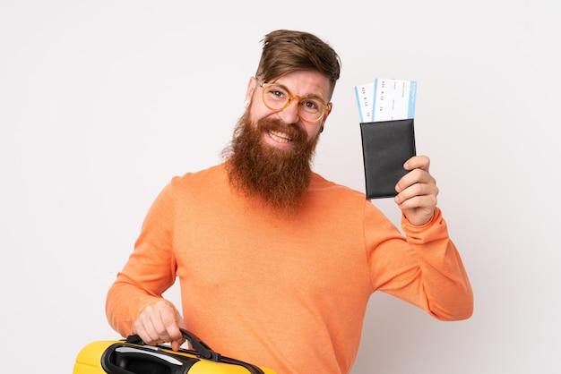 Homem ruivo com barba longa ao longo da parede branca em férias com mala e passaporte