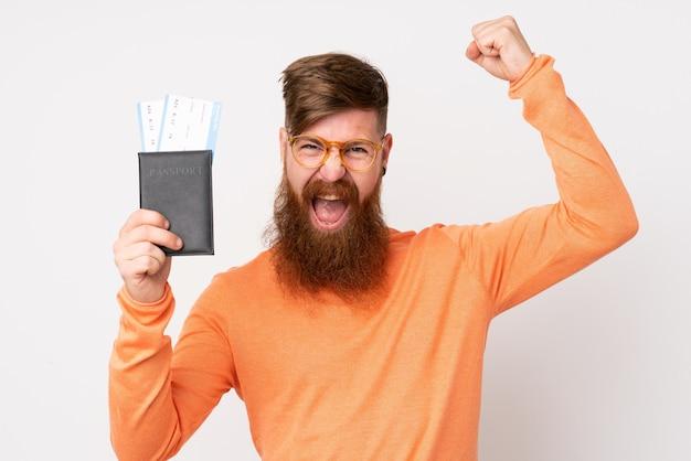Homem ruivo com barba longa ao longo da parede branca feliz em férias com bilhetes de avião e passaporte
