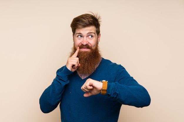 Homem ruivo com barba longa ao longo da parede isolada com relógio de pulso e pensando uma idéia