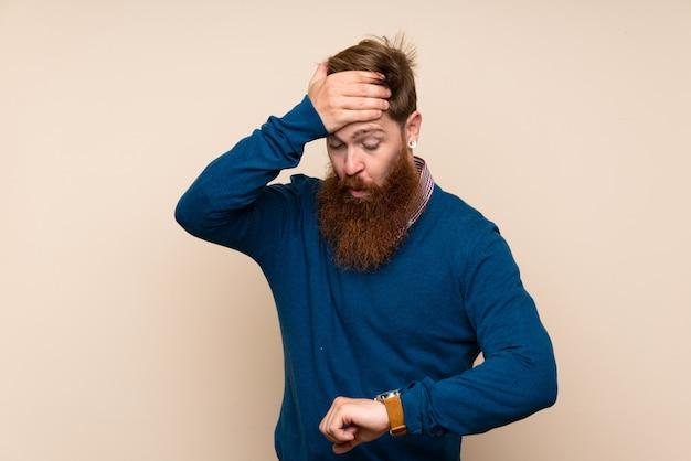 Homem ruivo com barba longa ao longo da parede isolada com relógio de pulso e surpreso