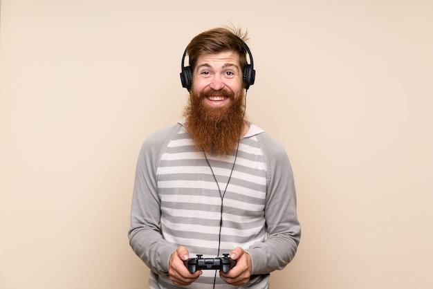 Homem ruivo com barba longa ao longo da parede isolada, jogando em videogames
