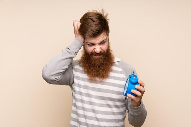 Homem ruivo com barba longa ao longo da parede isolada, segurando o despertador vintage