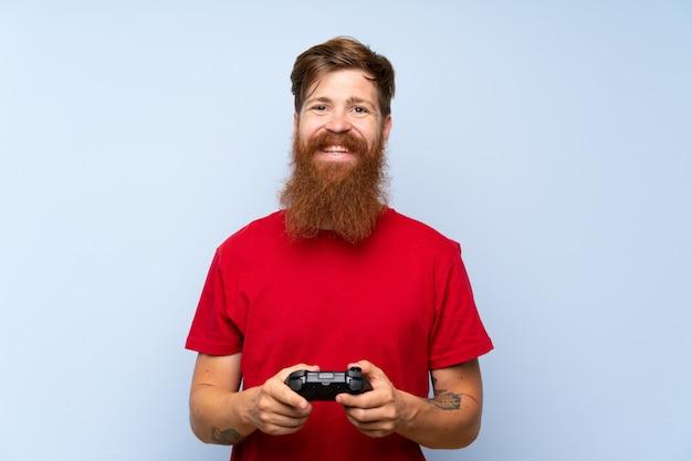 Homem ruivo com barba longa, brincando com um controlador de videogame, sorrindo muito