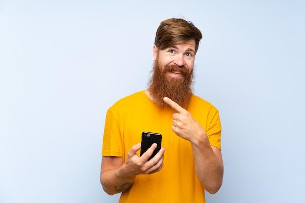 Homem ruivo com barba longa com um móvel sobre parede azul isolada, apontando para o lado para apresentar um produto