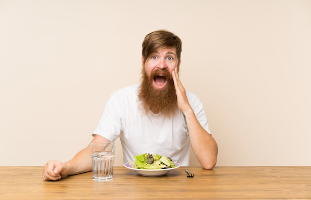 Homem ruivo com barba longa e com salada com surpresa e expressão facial chocada