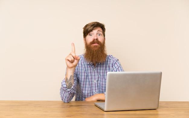 Homem ruivo com barba longa em uma mesa com um laptop apontando com o dedo indicador uma ótima idéia