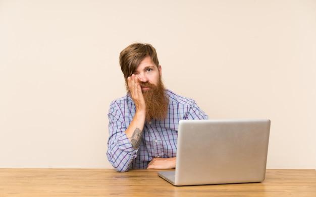 Homem ruivo com barba longa em uma mesa com um laptop infeliz e frustrado