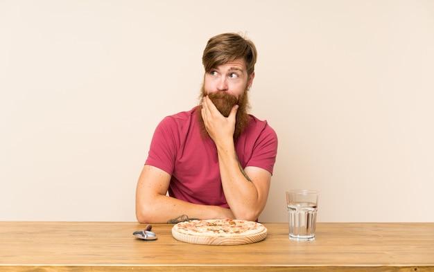 Homem ruivo com barba longa em uma mesa e com uma pizza pensando uma idéia