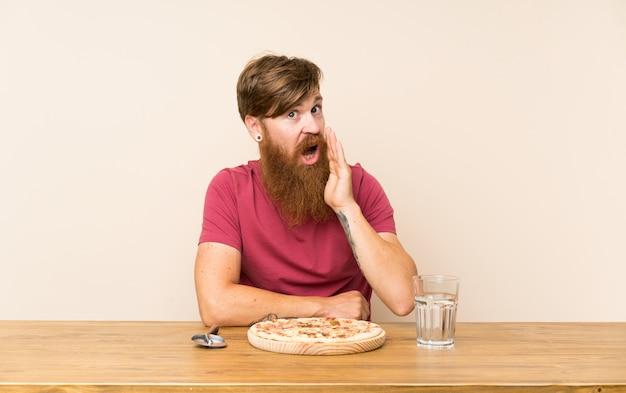 Homem ruivo com barba longa em uma mesa e com uma pizza sussurrando algo