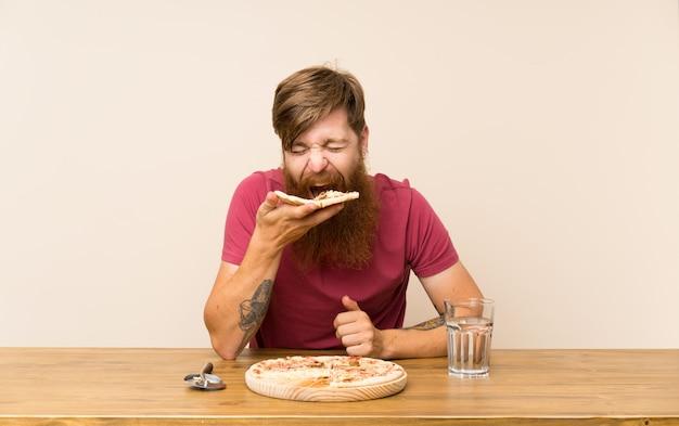 Homem ruivo com barba longa em uma mesa e com uma pizza