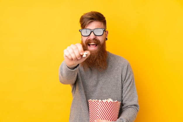 Homem ruivo com barba longa isolada parede amarela com óculos 3d e segurando um grande balde de pipocas enquanto apontando a frente