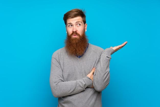 Homem ruivo com barba longa isolado azul infeliz por não entender algo