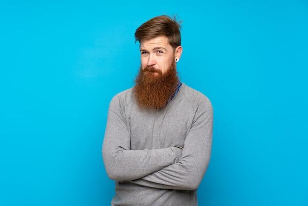 Homem ruivo com barba longa, isolado azul sentindo chateado
