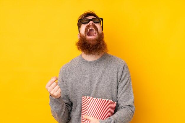 Homem ruivo com barba longa isolado parede amarela com óculos 3d e segurando um grande balde de pipocas