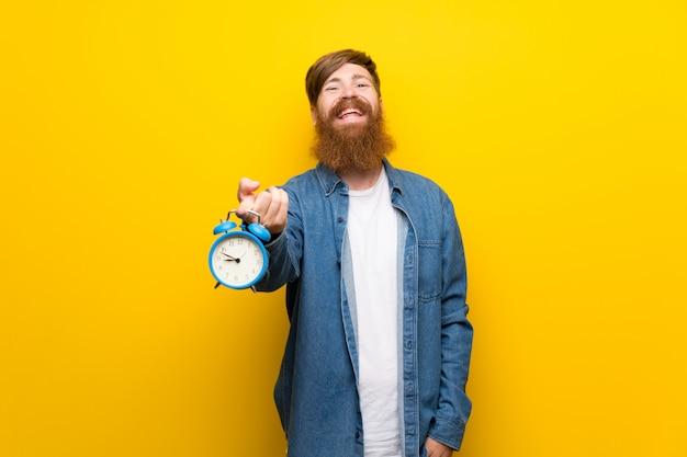 Homem ruivo com barba longa isolado parede amarela segurando o despertador vintage